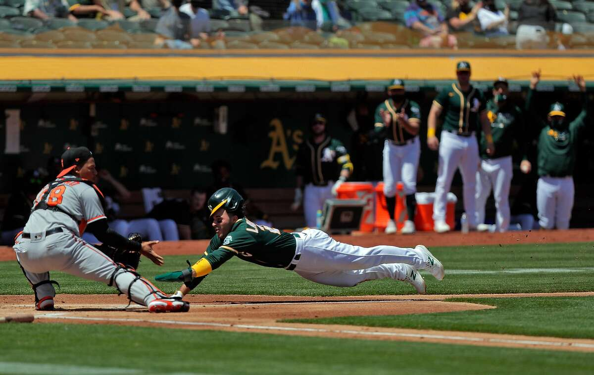 Ramon Laureano (22) dives toward home plante beating the throw home to catcher Pedro Severino (28) on a single by Matt Olson (28) in the first inning as the Oakland Athletics played the Baltimore Orioles at the Coliseum in Oakland, Calif., on Sunday, May 2, 2021.