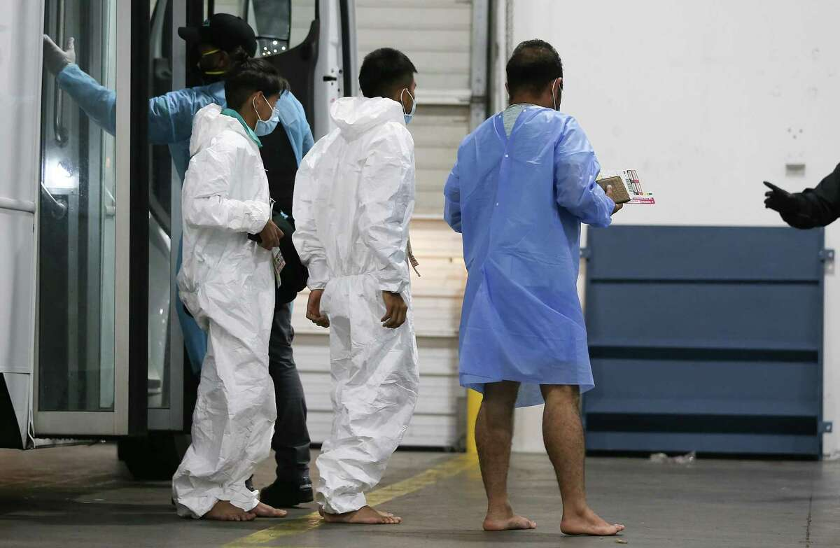 Men who were found in a southwest Houston home with over 90 people living in it are checked into a shelter in Houston on Friday, April 30, 2021.