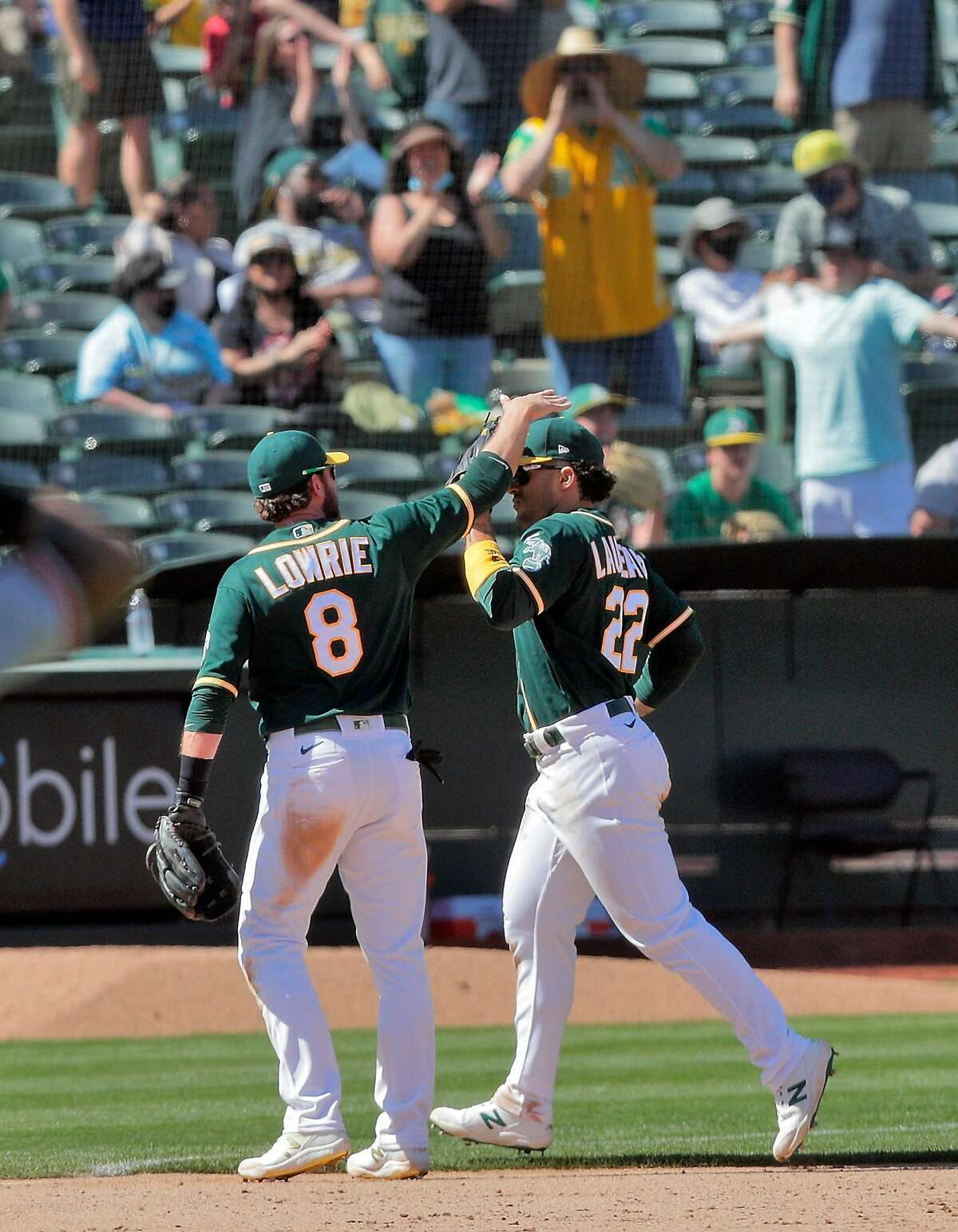 Ramon Laureano (right) gets a pat on the head from Jed Lowrie after making a leaping catch at the wall in the eighth inning to save a run. Laureano then homered in the bottom of the inning.