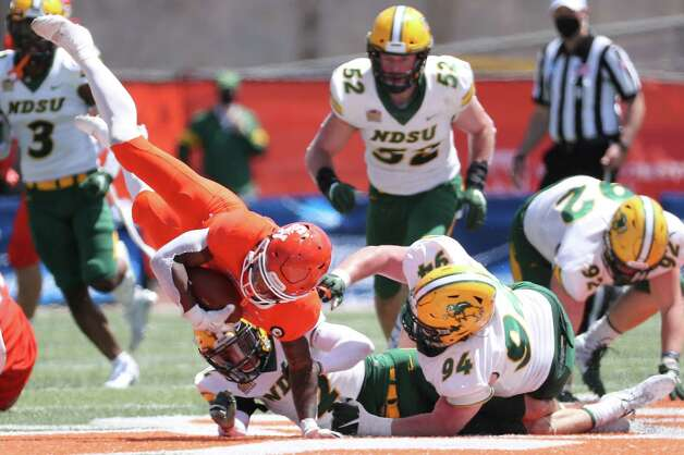 Sam Houston State running back Noah Smith (6) flies through the air after he is tripped up by North Dakota State safety Dawson Weber (2) and defensive tackle Costner Ching (94) after converting a first down during the first quarter of a quarterfinal game in the NCAA FCS football playoffs on Sunday, May 2, 2021, in Huntsville. Sam Houston advanced to the semifinals with a 24-20 win. Photo: Brett Coomer, Staff Photographer / © 2021 Houston Chronicle