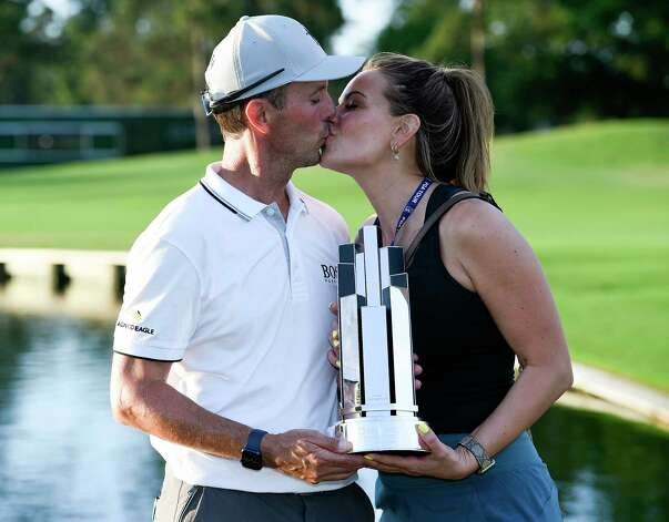 Mike Weir, left, kisses girlfriend, Michelle Money, while both hold the champions' trophy after winning the Insperity Invitational golf tournament, Sunday, May 2, 2021, in The Woodlands, TX. Weir won the tournament at -10, two shots better than John Daly, Tim Pretovic and David Toms. Photo: Eric Christian Smith, Contributor