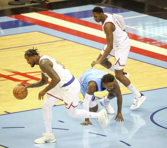 New York Knicks forward Julius Randle (30) gets the ball away from Houston Rockets forward Jae'Sean Tate (8) as New York Knicks guard RJ Barrett (9) runs past during the first quarter of an NBA game Sunday, May 2, 2021, at the Toyota Center in Houston. Photo: Jon Shapley, Staff Photographer / © 2021 Houston Chronicle