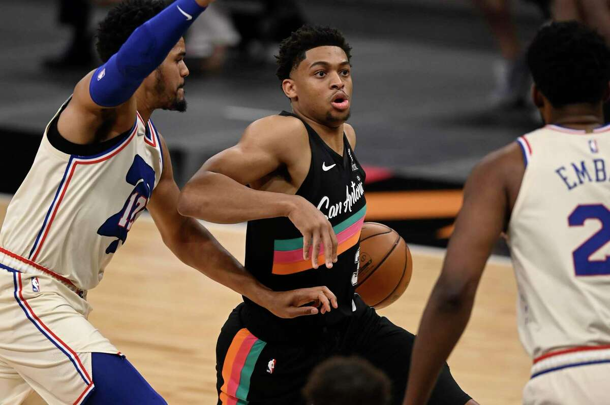 Spurs' Keldon Johnson, center, drives against Philadelphia 76ers' Tobias Harris, left, and Joel Embiid during the first half of an NBA basketball game on Sunday, May 2, 2021, in San Antonio.
