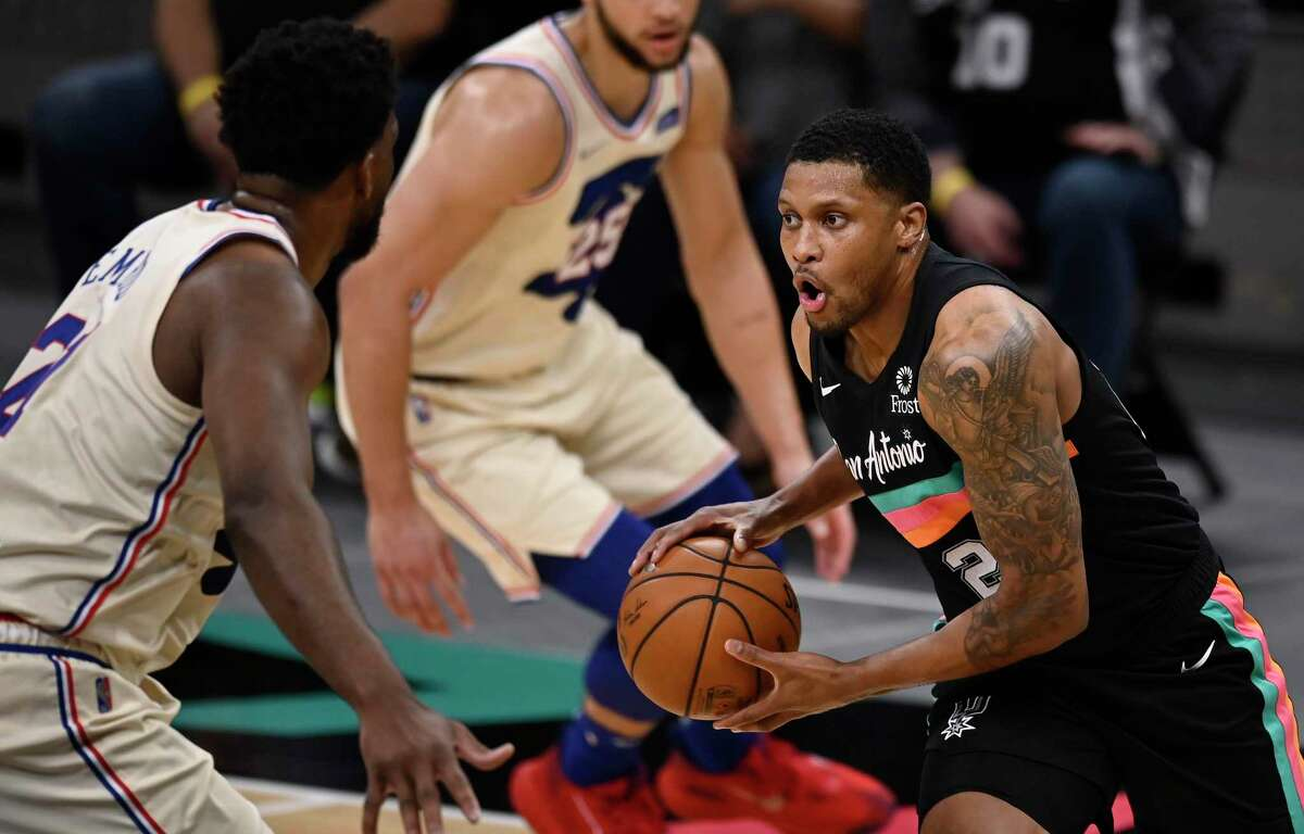 Spurs' Rudy Gay, right, drives against Philadelphia 76ers' Joel Embiid during the first half of an NBA basketball game on Sunday, May 2, 2021, in San Antonio.