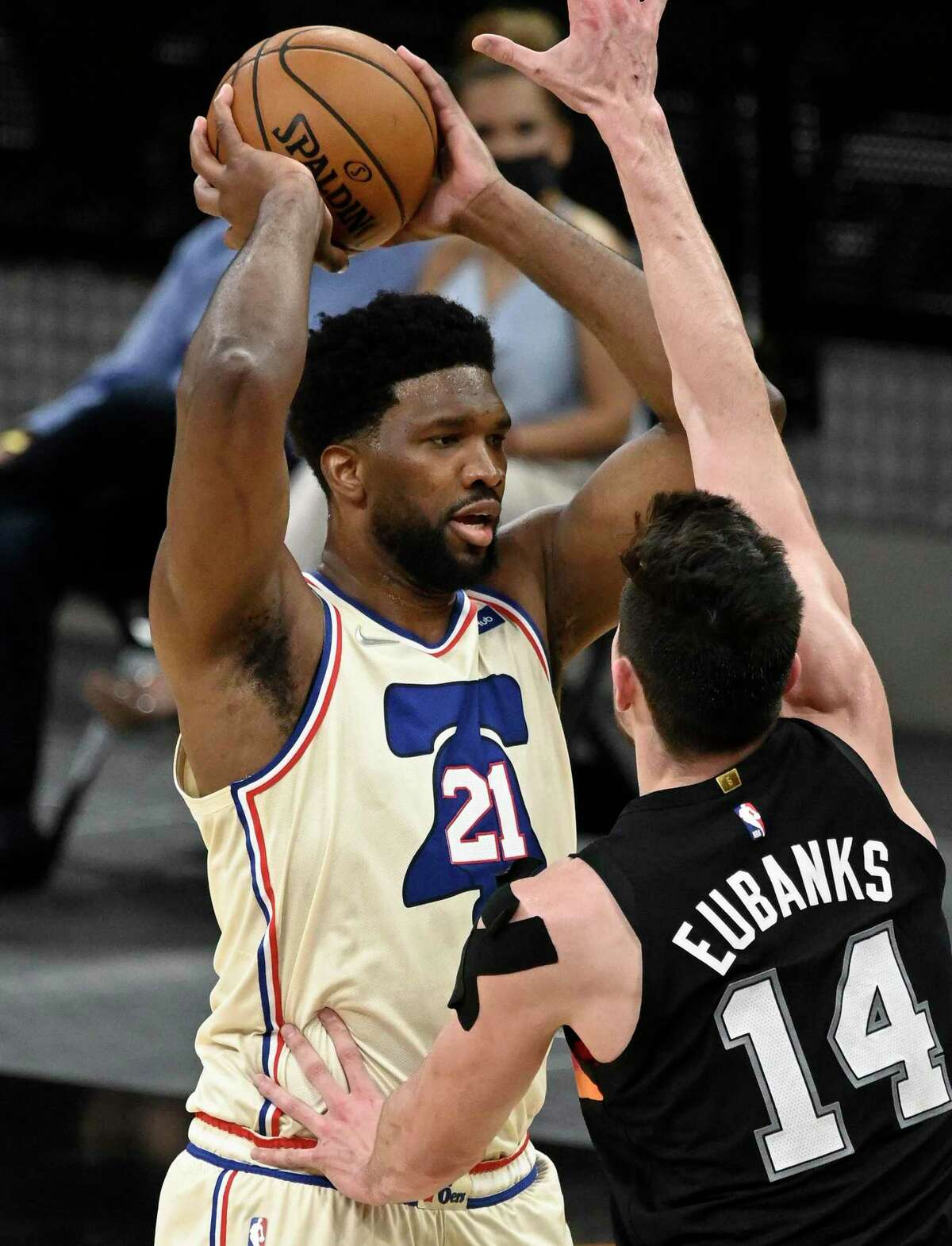 Philadelphia 76ers' Joel Embiid (21) looks to pass as he is defended by the Spurs' Drew Eubanks during the second half of an NBA basketball game on Sunday, May 2, 2021, in San Antonio.