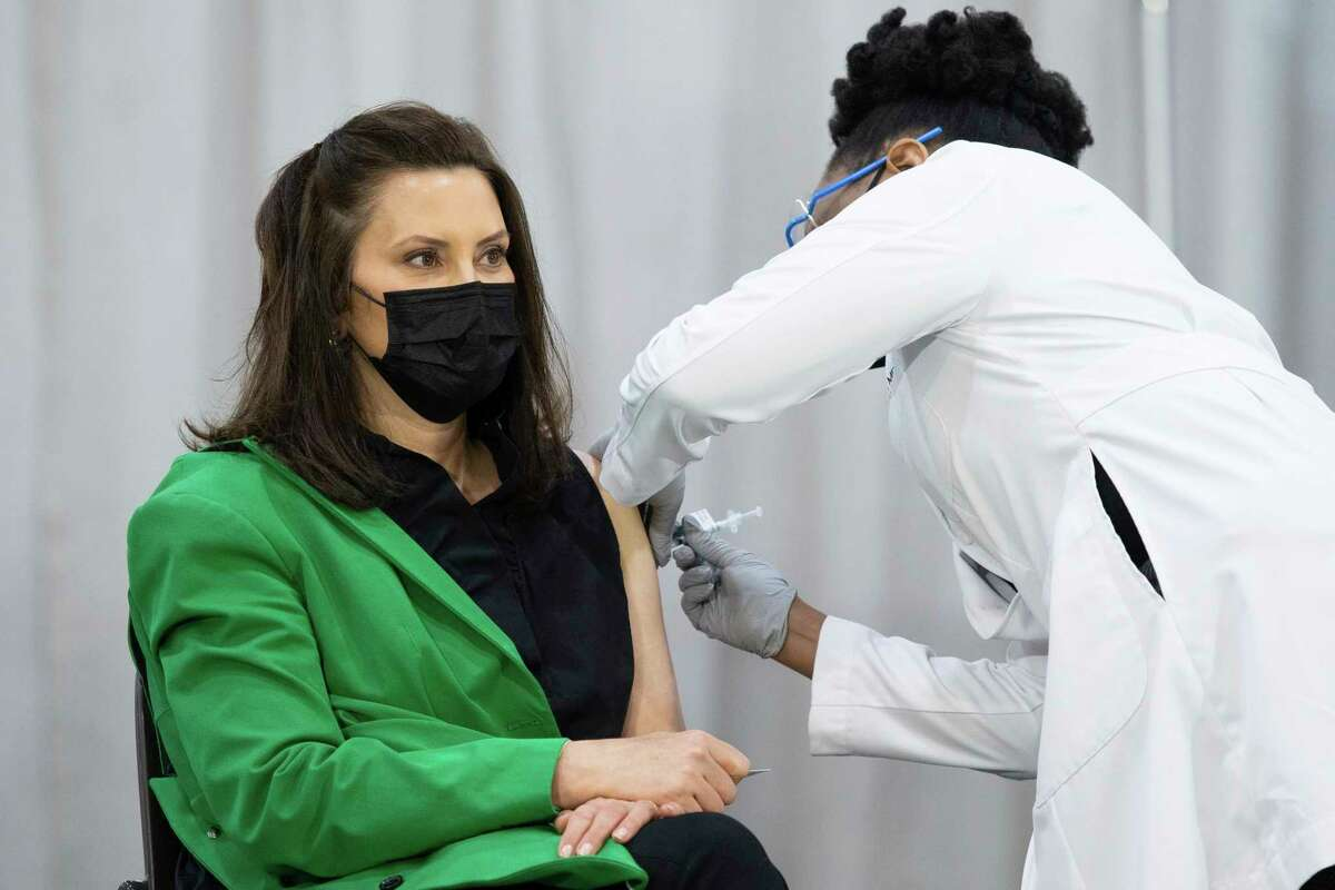 Michigan Gov. Gretchen Whitmer receives her second dose of Pfizer's COVID-19 vaccine from Dr. Joneigh Khaldun at DeVos Place on Thursday, April 29, 2021, in Grand Rapids, Mich. (Hope Davison/The Grand Rapids Press via AP)