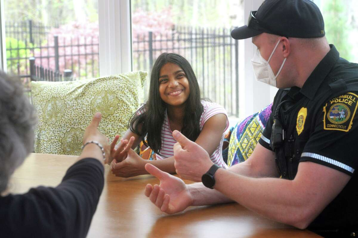 Teesa Arden, who is deaf, uses sign language to communicate with Trumbull Police Officer Derek Laaser, right, and Jill Angotta, left, her teacher for the deaf from the Trumbull schools during an interview in Arden's home in Trumbull, Conn. April 29, 2021.