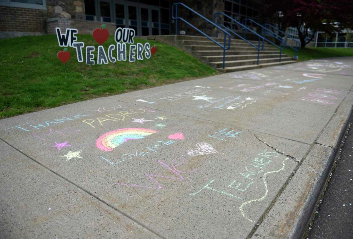 Students and parents write thank you messages in sidewalk chalk outside Northeast Elementary School in Stamford on Sunday. To kick off Teacher & Staff Appreciation Week at Northeast, families were invited to participate in the tradition of
