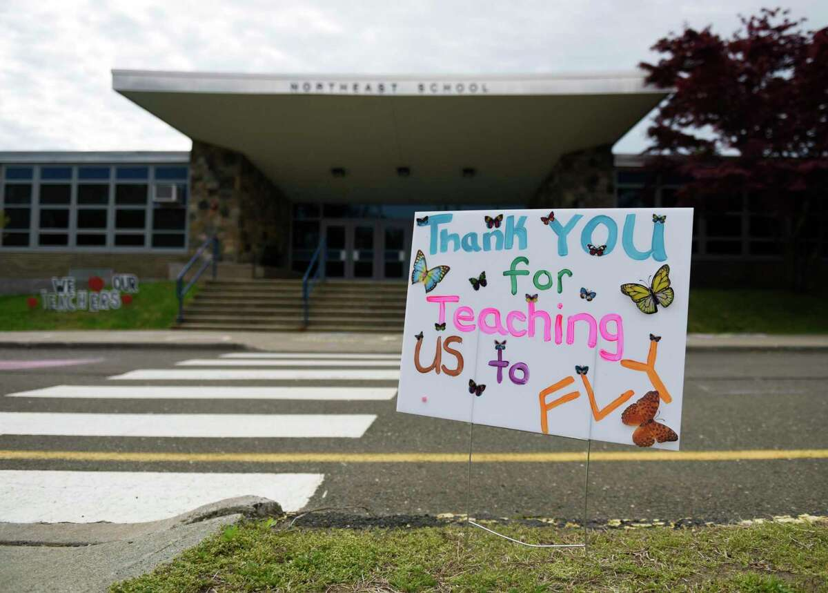 Students and parents write thank you messages in sidewalk chalk outside Northeast Elementary School in Stamford, Conn. Sunday, May 2, 2021. To kick off Teacher & Staff Appreciation Week at Northeast, families were invited to participate in the tradition of