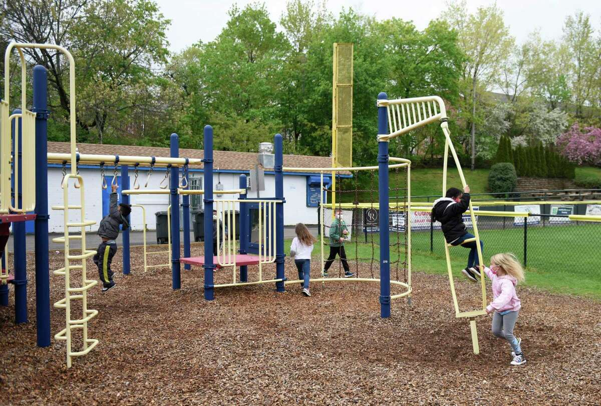 Children play on the playground during recess at Springdale Elementary School in Stamford, Conn. Thursday, April 29, 2021. Stamford schools re-opened playgrounds this week for the first time since the beginning of the pandemic.