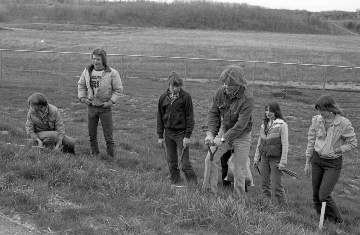 Ninth graders from Manistee High School's general biology class planted trees Friday to provide a windbreak at the MHS tracks. The trees, donated by Packaging Corporation of America, are expected to grow six to eight feet the first year after planting. The photo was published in the News Advocate on May 4, 1981. (Manistee County Historical Museum photo)