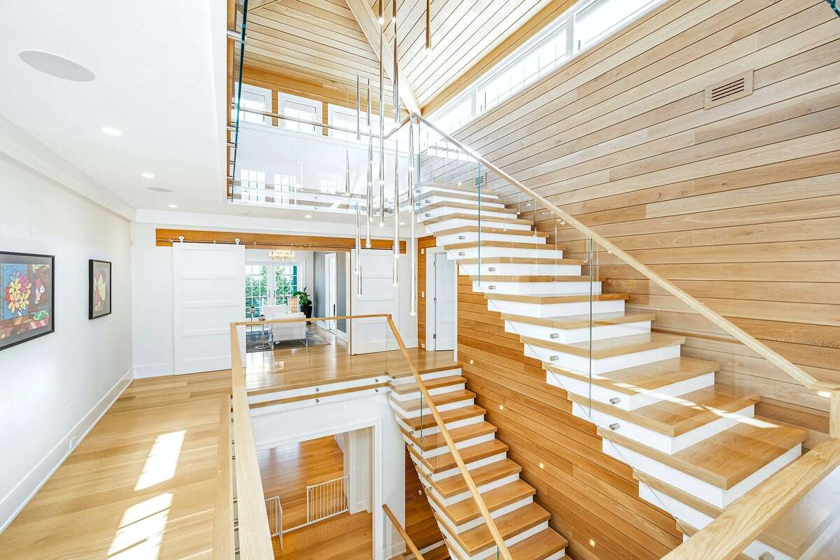 The glass-enclosed floating staircase in the Shore Road home descends through all four levels and feels