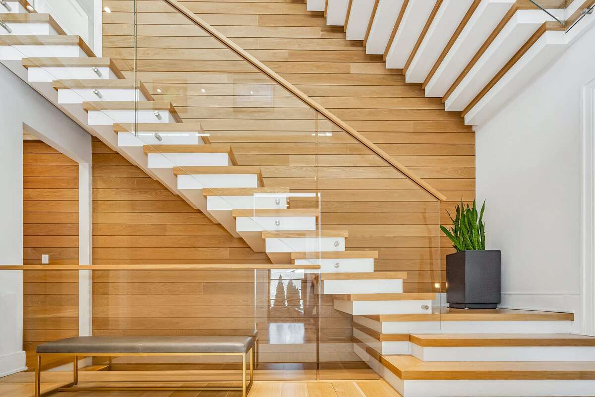 The modern glass-enclosed floating staircase makes the Shore Road home feel