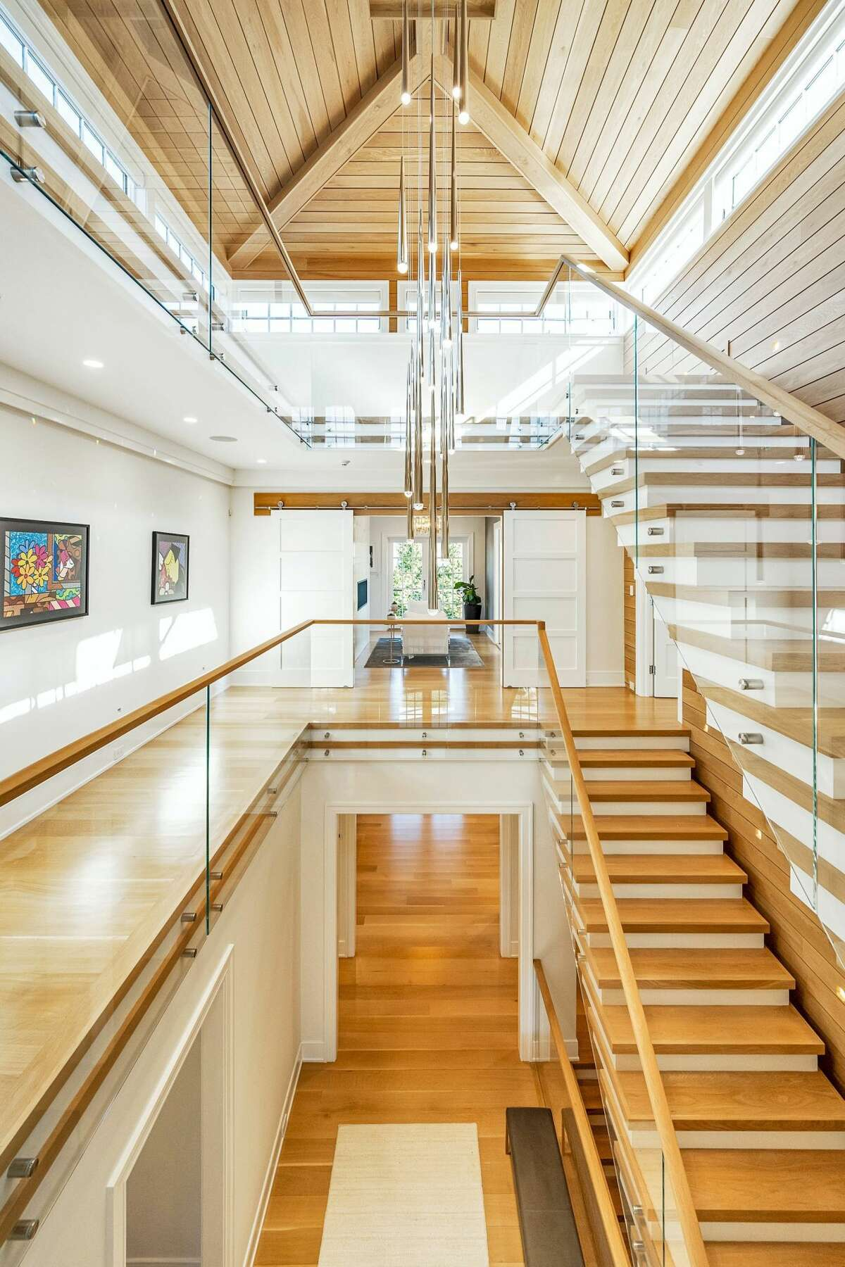 The floating stairs in the Old Greenwich home are enclosed by glass railings and connect all four levels of living. View listing
