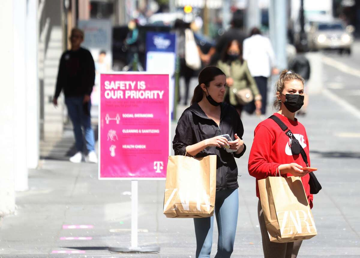 Pedestrians carry shopping bags as they walk through the Union Square shopping district on April 15, 2021, in San Francisco.