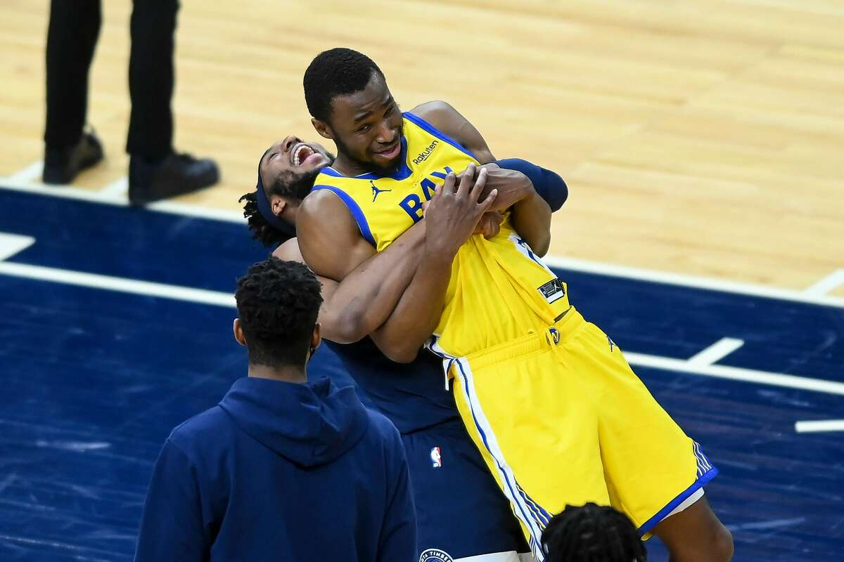 Minnesota Timberwolves forward Josh Okogie (20) gives an unexpected lift to former teammate Golden State Warriors forward Andrew Wiggins (22) after Thursday night's game April 29, 2021 at Target Center in Minneapolis, Minnesota. (Aaron Lavinsky/Minneapolis Star Tribune/TNS).
