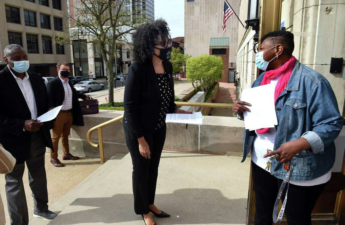 From left, campaign treasurer Donald McAuley Sr., and campaign manager Will Viederman watch Karen DuBois-Walton drop off paperwork to run for mayor with Deputy City Clerk May Gardner-Reed in front of the Hall of Records in New Haven on May 3, 2021.