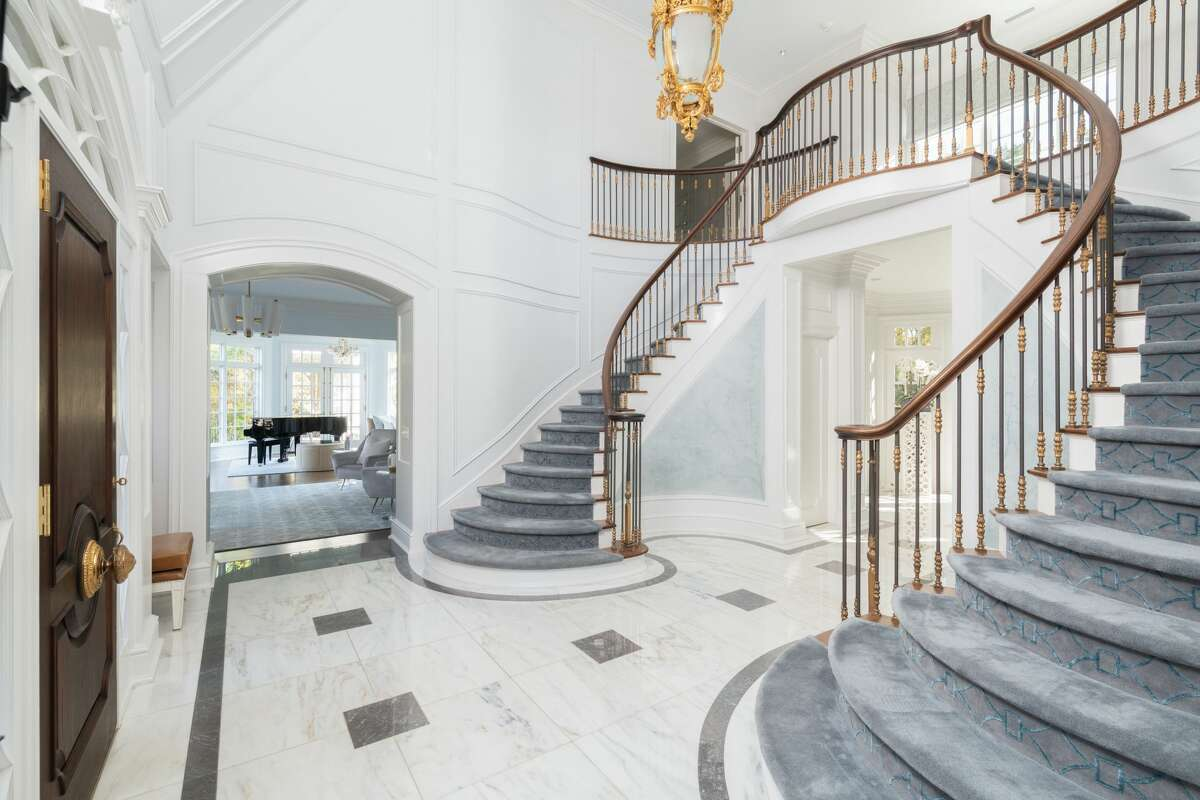 marble entrance foyer with butterfly staircase at 36 Hemlock Hill Road, New Canaan.