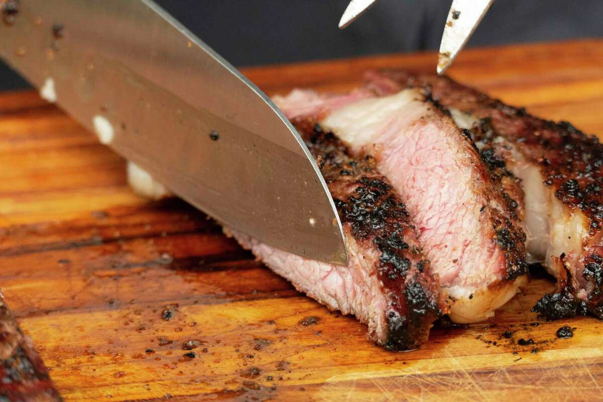 Steak is sliced on a cutting board after being reverse seared on both a smoker and a grill. The process exposes the steaks to low heat to cook them to the proper internal temperature.