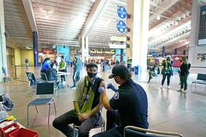FILE - In this May 2, 2021, file photo, Austin Kennedy, left, a Seattle Sounders season ticket holder, gets the Johnson & Johnson COVID-19 vaccine at a clinic in a concourse at Lumen Field prior to an MLS soccer match between the Sounders and the Los Angeles Galaxy. Air travel in the U.S. hit its highest mark since COVID-19 took hold more than 13 months ago, while European Union officials are proposing to ease restrictions on visitors to the continent as the vaccine rollout sends new cases and deaths tumbling in more affluent countries.