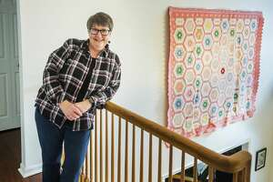 Lisa Quencer poses for a portrait alongside one of her quilts Friday, Feb. 12 at her home in Midland. (Katy Kildee/kkildee@mdn.net)