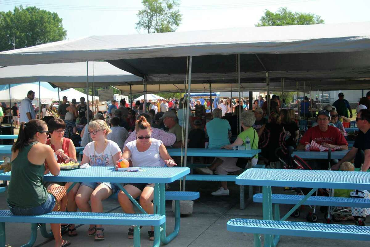Folks eat their fish sandwiches at picnic tables at the 2019 edition of the Bay Port Fish Sandwich Festival. The local tradition will return in August 2021, but will mainly offer take-out meals instead. (Tribune File Photo)