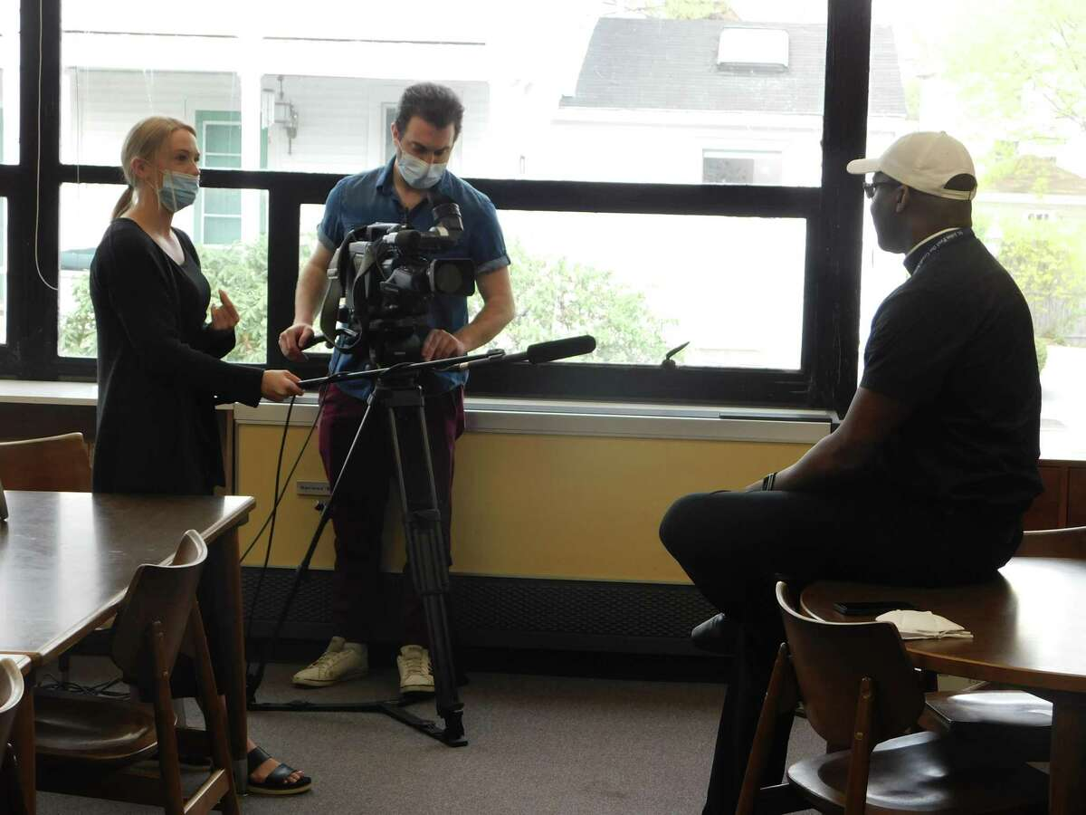 """From left, Kaelee Collins and Zach Wehner of Crossroads Magazine interview Father Emmanuel Ihemedu, pastor of St. John Paul the Great Parish, about """"Takeout Tuesdays,"""" a fundraising partnership with St. John Paul the Great Academy and local restaurants."""