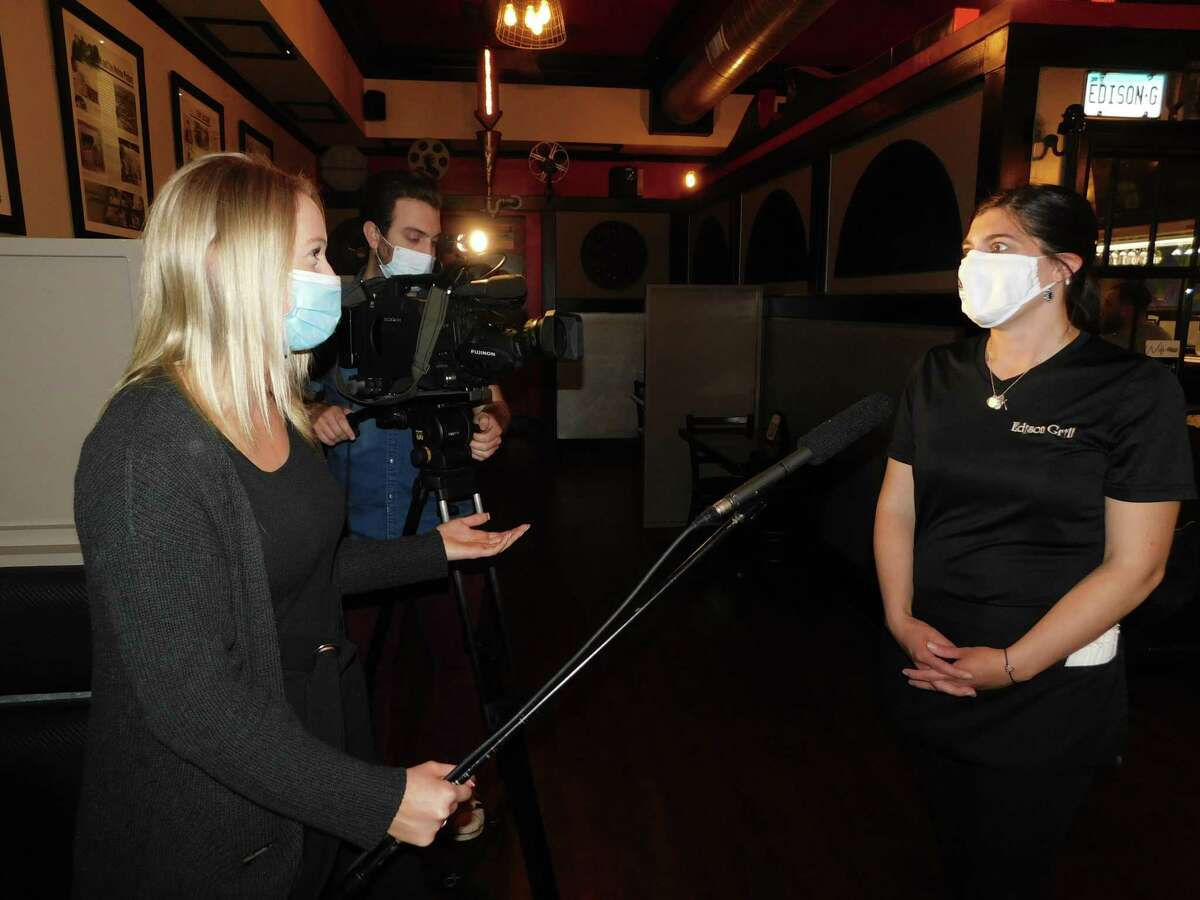 """From left, Kaelee Collins and Zach Wehner of Crossroads Magazine interview Chrissy Pagano, a server at Edison Grill in Harwinton, about """"Takeout Tuesdays,"""" a fundraising partnership with St. John Paul the Great Academy and local restaurants."""