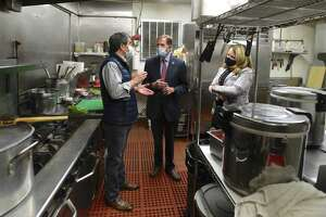 Wilson Hernandez,left, owner of La Mitad de Mundo Restaurant, talks with U.S. Senator Richard Blumenthal and Catherine Marx, right, SBA District Director for Ct Office, in his restaurants kitchen. Blumenthal and Marx were there to highlighted new federal assistance available to restaurants Danbury, Conn, on Monday, May 3, 2021.