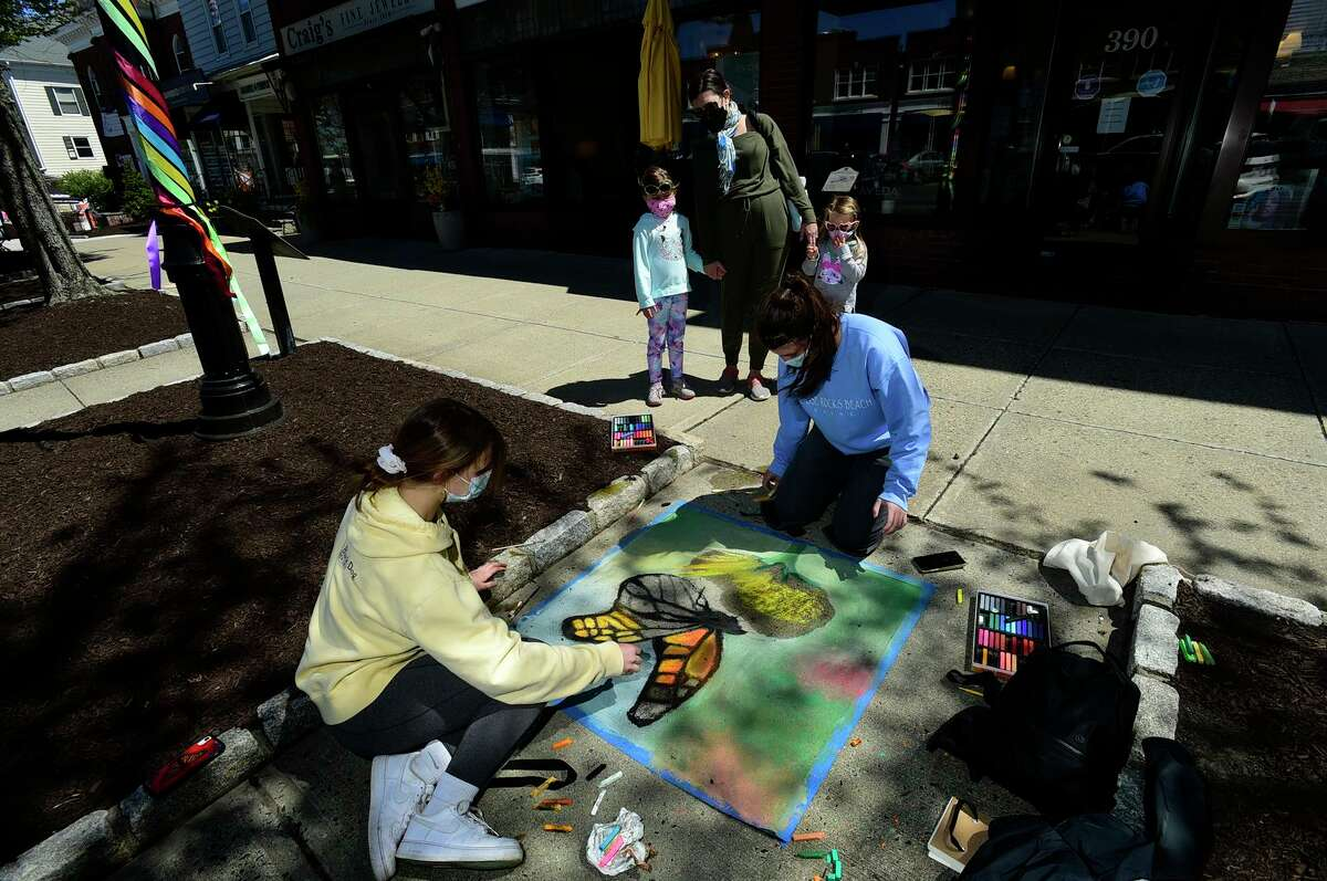 Resident Tonja Dias and her kids, Riley, 6, and Cora, 4, watch as Ridgefield High School students Sofia Daigle and Emily Brown create a chalk drawing of a monarch butterfly on Main Street during Downtown Ridgefield's 2021 Spring Stroll.