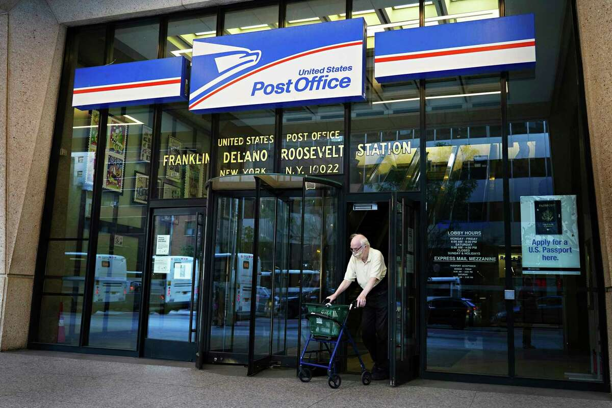 A man wearing a protective mask exits a U.S. Post Office in New York on August 18, 2020. (Cindy Ord/Getty Images/TNS)