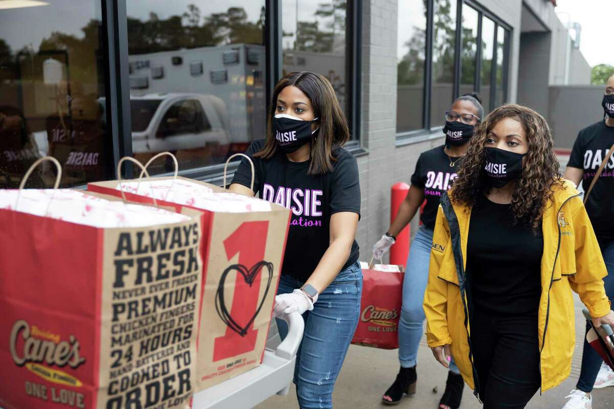 Julie Hightower, executive board member of the Daisie Foundation, left, rolls a cart of Raising Cane's into the Conroe Hospital alongside Deneen Newman, during their Houston Hospital Giveback Day, Friday, April 30, 2021, in Conroe.The Daisie Foundation will host giveaway events for mother's and first responders until May 2 throughout the Greater Houston Area.