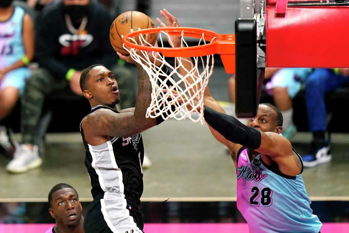 Spurs guard Lonnie Walker IV shoots as Heat forward Andre Iguodala (28) defends during the second half of an NBA basketball game, Wednesday, April 28, 2021, in Miami. The Heat won 116-111.