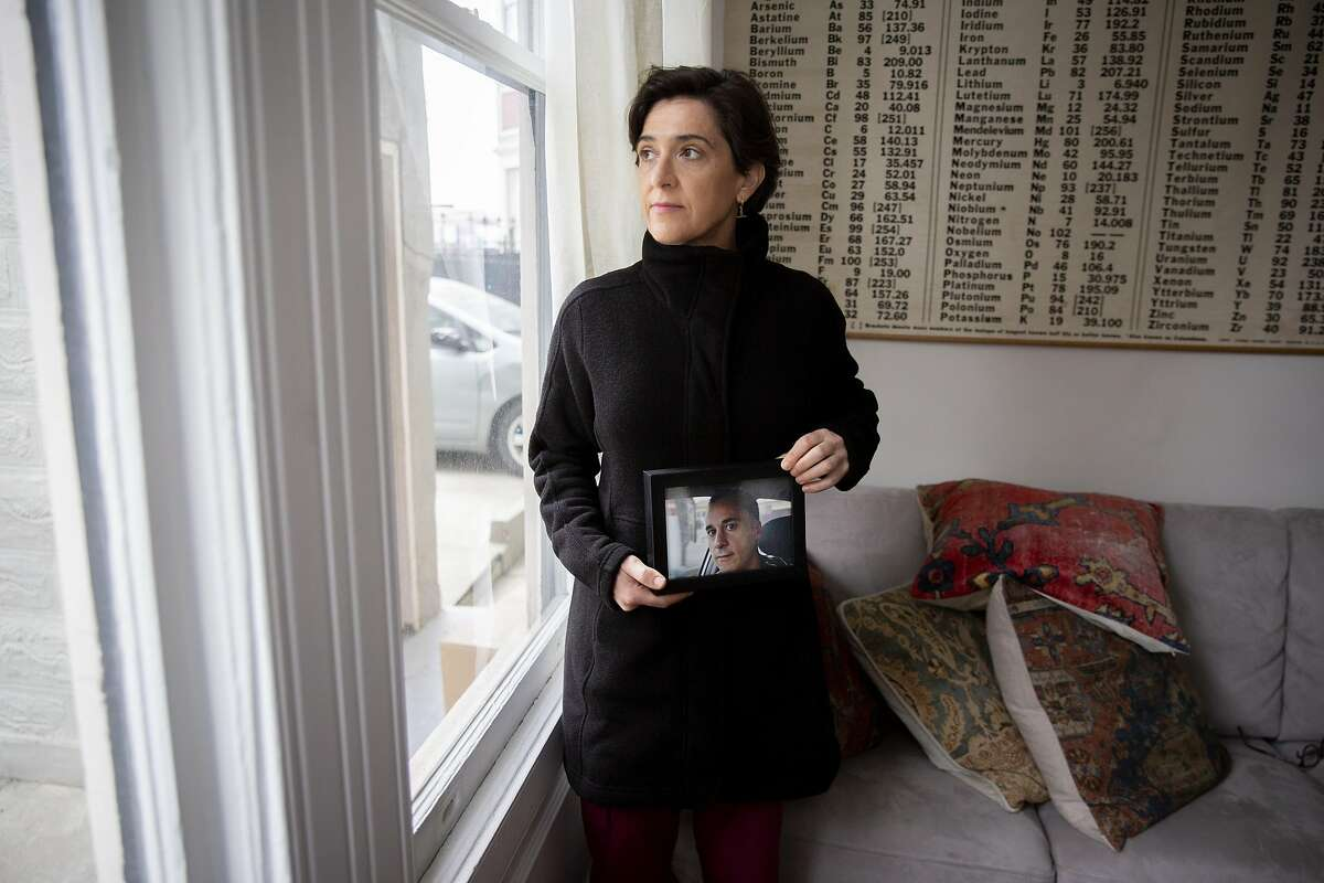 Vera Ares holds a photo of her late husband Gustavo Pesce at her home in San Francisco.