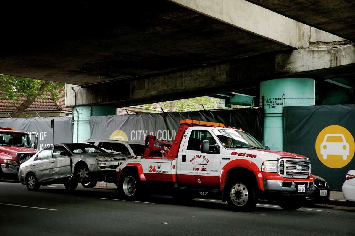 A tow truck impounds a car to the AutoReturn impound facility in San Francisco.