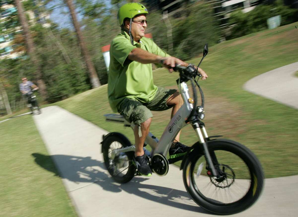 Advocates of electric bicycles, stand-up scooters and skateboard-like vehicles want The Woodlands to change a policy that bans motorized vehicles on the more than 200 miles of walking and bicycling paths. In this file image, Robert Solana, owner of ECO EZ-Riders in The Woodlands, demonstrates one of the company's electric bicycles. However, Solana no longer rents the 'e-bikes.'