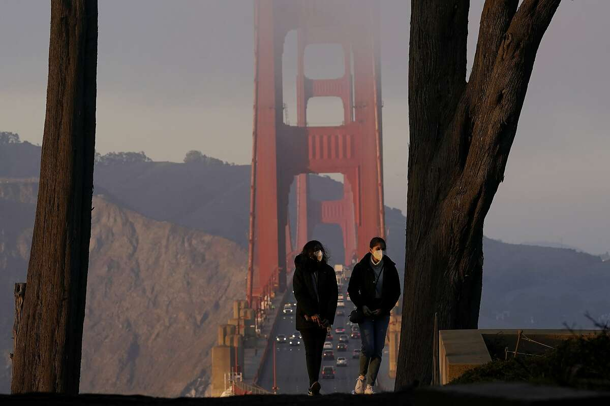 In this Dec. 21, 2020, file photo, people wear face masks near the Golden Gate Bridge. California's Department of Public Health says face coverings are no longer required outdoors for fully vaccinated people except in crowded settings.