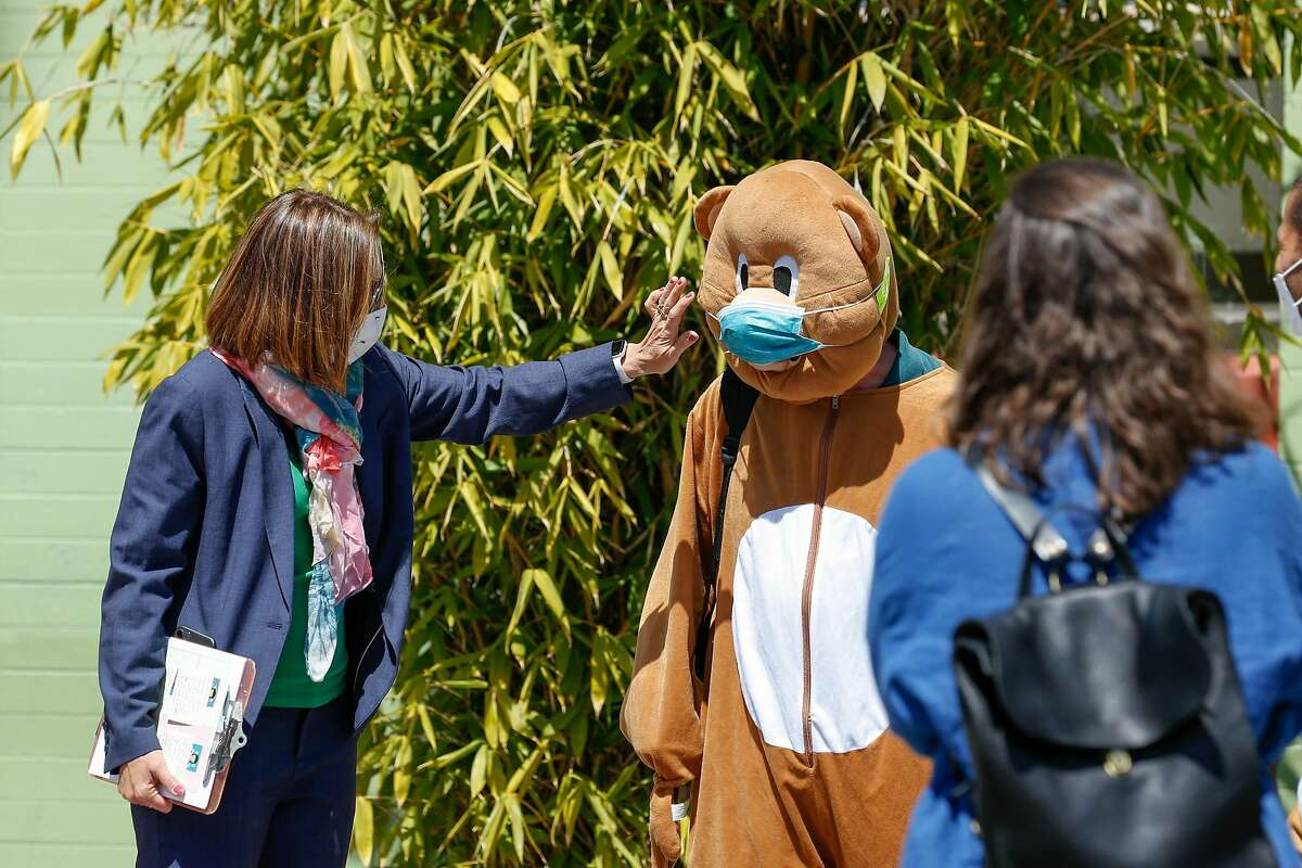 Bryan Elementary School principal Laura Codicetti adjusts the mask on the school mascot just before a news conference on in-person learning at the school April 9, 2021. On Monday, California lifted its requirement for outdoor mask-wearing for fully vaccinated people.