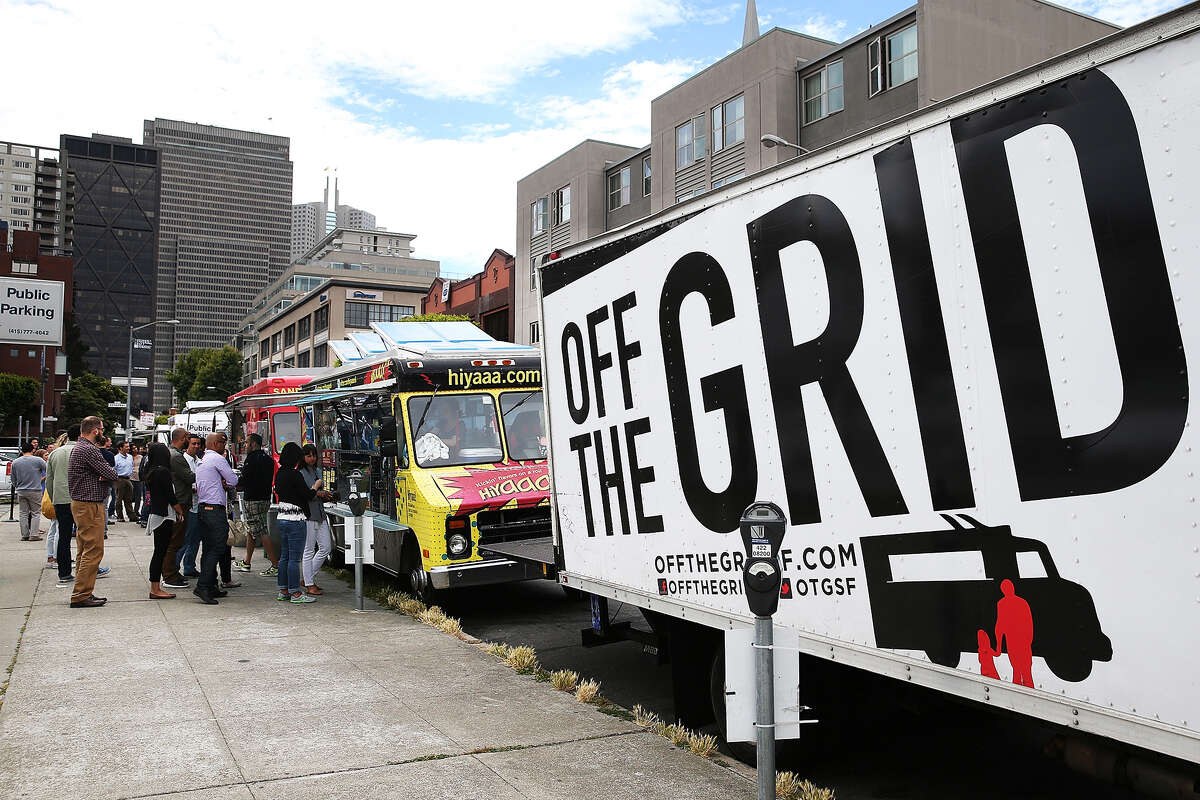 """Food trucks line Front Street during an Off the Grid """"market"""" in San Francisco, Calif."""