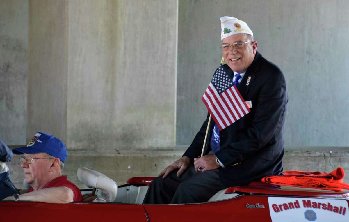 Tom Flowers, chairman of the Memorial Day Parade in Milford, Conn., May 26, waves to parade-goers as he makes his way along the parade route in 2019.