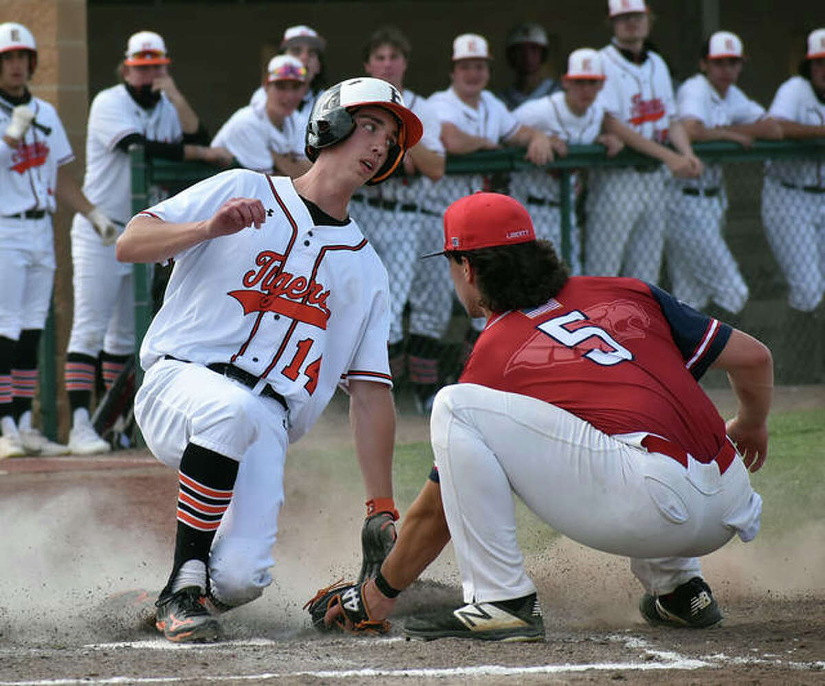 Edwardsville's Kyle Modrusic slides safely into home plate ahead of the tag against Liberty on Monday at Tom Pile Field in Edwardsville.