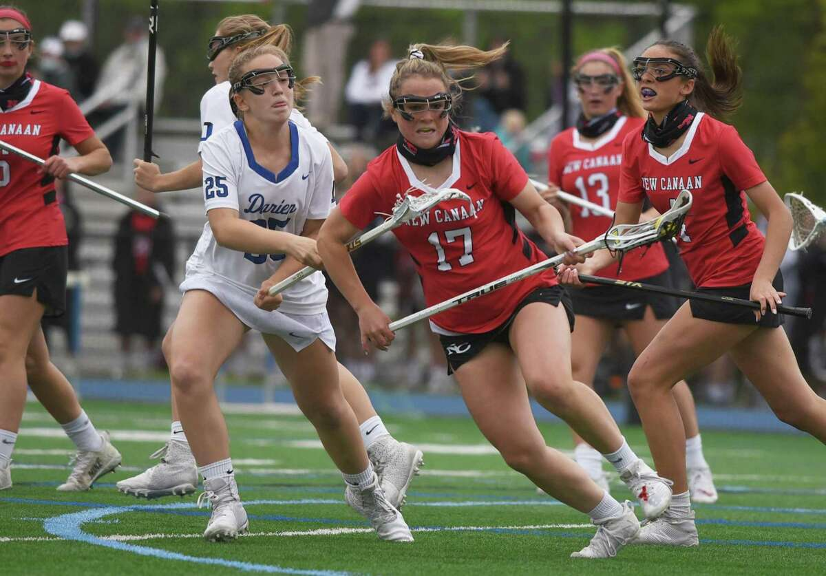 New Canaan's Courtney O'Connell (17) and Darien's Kate Avitabile (25) battle for the ball during the Rams' 10-9 overtime victory at Darien on Monday.