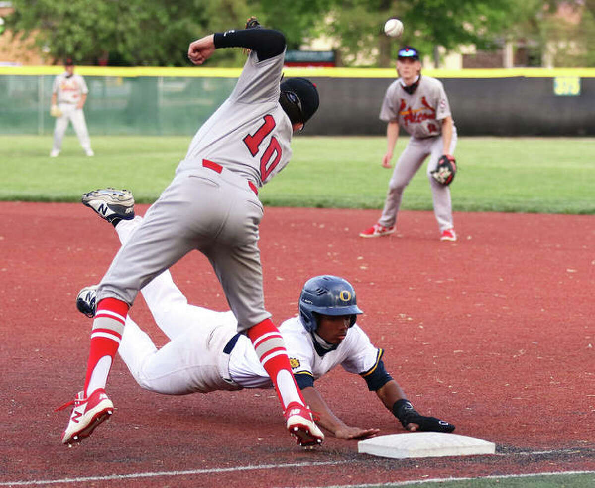 O'Fallon's Kellen Scruggs dives back to the bag while Alton first baseman Owen Macias (10) cannot get to a high and wide pickoff throw Monday at Blazier Field in O'Fallon.