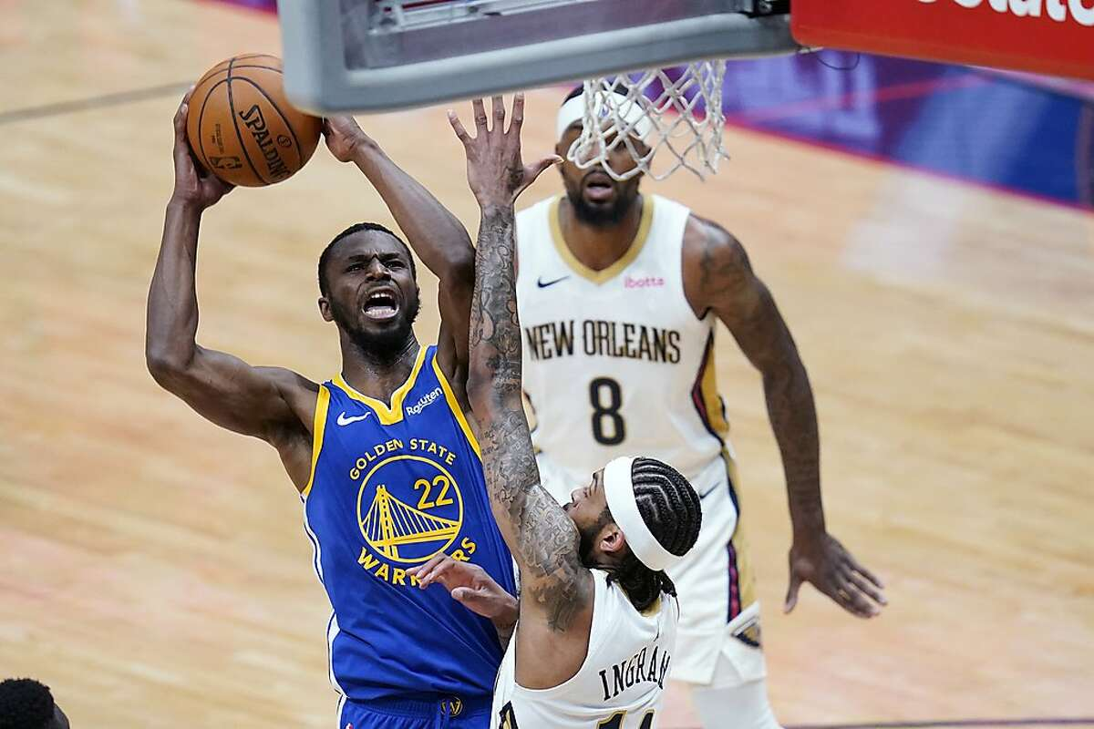 Golden State Warriors forward Andrew Wiggins (22) goes to the basket between New Orleans Pelicans forward Brandon Ingram and forward Naji Marshall (8) in the first half of an NBA basketball game in New Orleans, Monday, May 3, 2021. (AP Photo/Gerald Herbert)