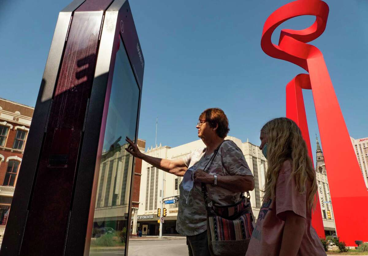 """Debbie St. Clair and her granddaughter, Cora, use an IKE kiosk in downtown San Antonio to find information on Monday, May 3, 2021. The City of San Antonio uses the kiosks to deliver information to pedestrians, both locals and tourists. The sculpture called """"La Antorcha de la Amistad"""" by Mexican artist Sebastián, is at right."""