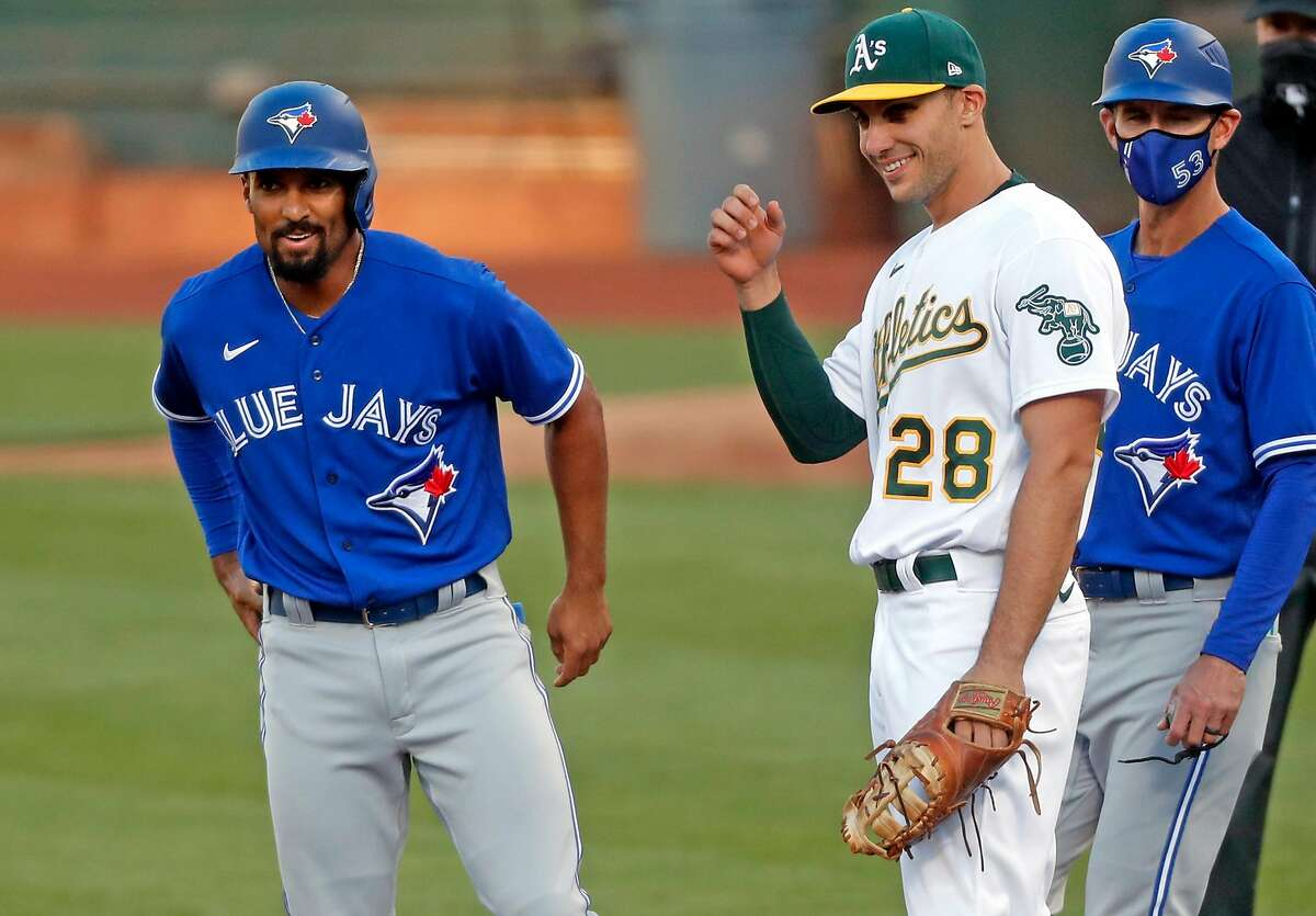 Blue Jays second baseman Marcus Semien shares a light-hearted moment at first base with his ex-teammate, Matt Olson, after a second-inning walk. Semien spent six seasons with the A's.