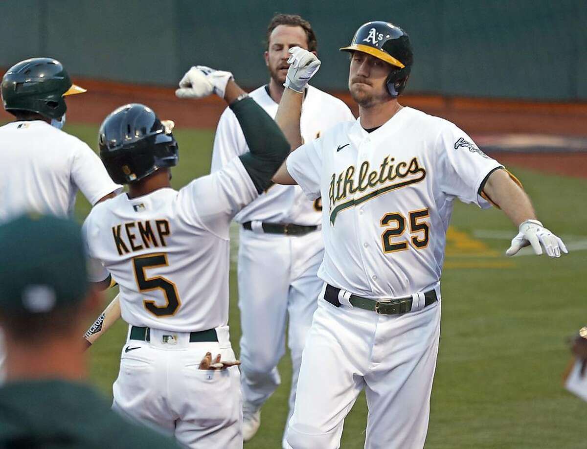 After hitting a 2-run home run, Oakland Athletics' Stephen Piscotty arm bumps Tony Kemp in 2nd inning against Toronto Blue Jays during MLB game at Oakland Coliseum in Oakland, Calif., on Monday, May 3, 2021.