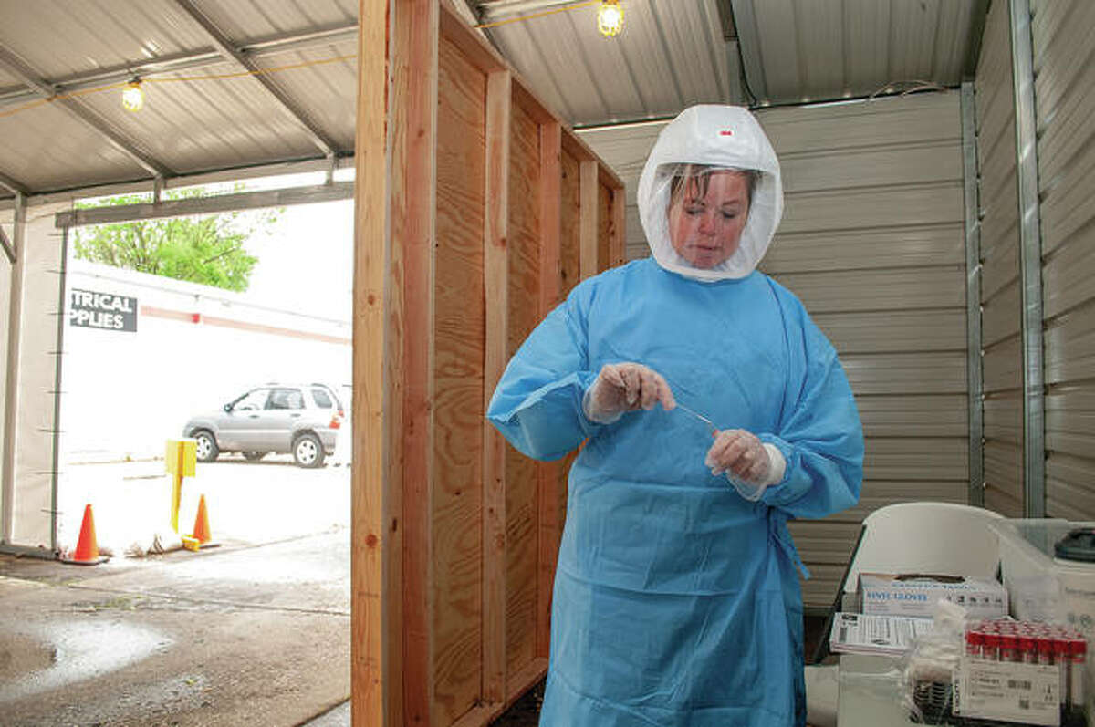 Morgan County Health Department volunteer Marsha Allen places a cotton swab in a test tube at a COVID-19 drive-through testing site. As demand declines for virus tests, some county health agencies are considering changes to scheduling.