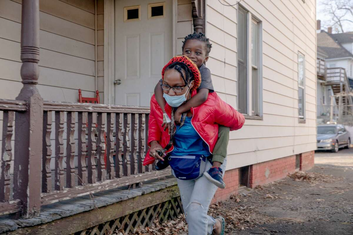 """Moneisha Bryan runs with her youngest son, Myron Hodges Jr., 4, on her back. """"Now I'm fine with not knowing,"""" Bryan said. """"So now, [I'm] accepting myself and still working towards my goal... That's how I'm different after the pandemic."""""""