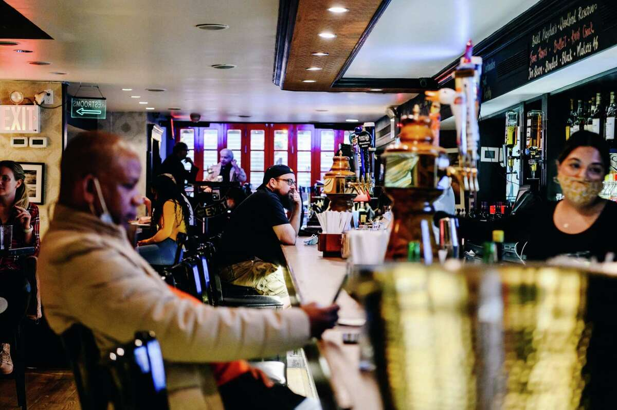 Customers sit at the bar at Blooms Tavern in New York on May 3, 2021.